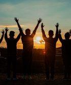 personas de diferentes géneros levantando las manos